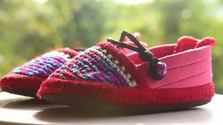 sapato : knitted baby shoes with embroidered national with ties rotate on the background greenery