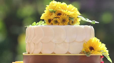 wedding cake : white creamy cake decorated with yellow chrysanthemum flowers rotates