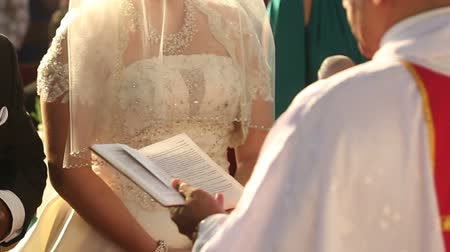templombúcsú : Catholic priest read divine oath before indian groom tuxedo and bride in white dress at the wedding
