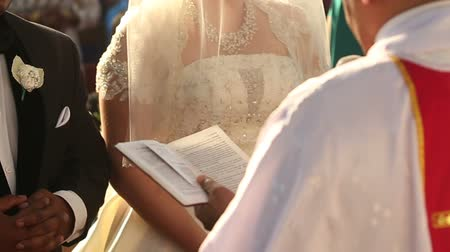 rahip : Catholic priest read divine oath before indian groom tuxedo and bride in white dress at the wedding