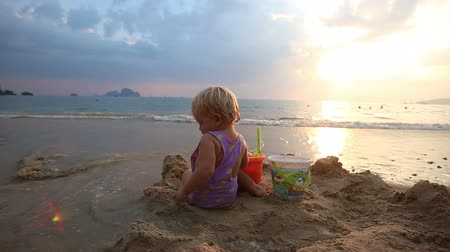 zamek : child play with bucket and shovel in the middle of the ruined castle of sand at sunset