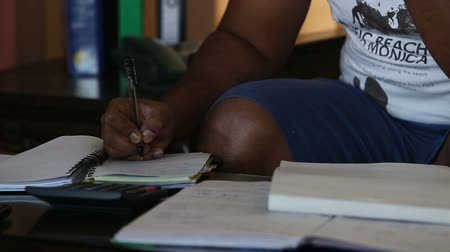 darkskinned : dark-skinned man is writing notes with a pen in a pad when sitting at coffee table