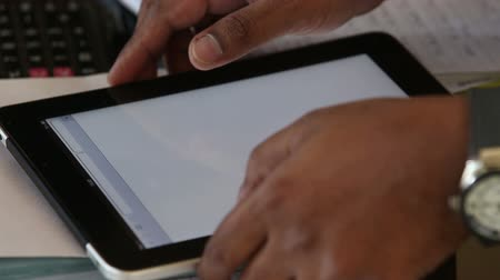 darkskinned : a dark-skinned man is holding a tablet  on the table and waiting for loading brouser