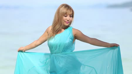 opalenizna : beautiful blonde asian girl waving transparent blue dress and smiles at the background of azure sea and cliffy island