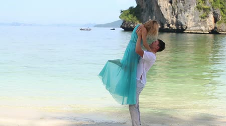 erkek güzellik : strong guy lifts pretty blonde asian girl over his head and kisses at the background of azure sea and rocky island