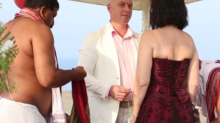 dospělý : hindu brahmins are conducting indian wedding ceremony in front of white people stretching shawl between them and they are holding mango leaves necklace Dostupné videozáznamy