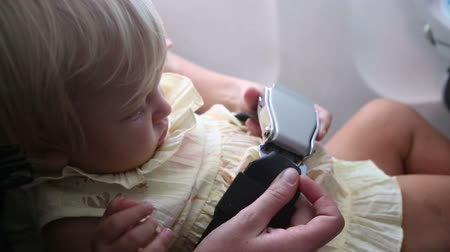 mother fastens and unfastens the safety belt buckle on her small daughter in the airplane Vídeos
