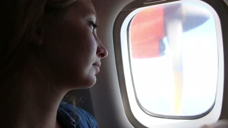 olhares : young beautiful woman with small child sitting on her knees looks out of airplane window at floating past engine propeller clouds Vídeos
