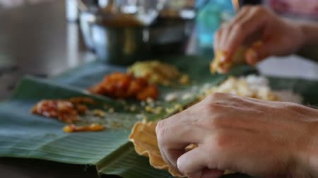 pani : white man eats indian rice with flat cake from banana leaf as the indian people and focus is changes Stock Footage