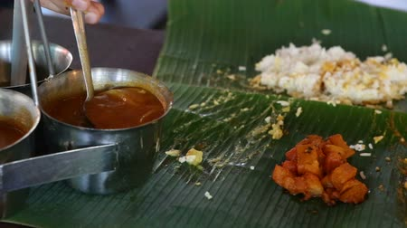 pani : white man pours out dressings onto Indian food on banana leaf like Indian people
