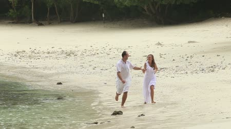 nedves : blonde bride and handsome groom running along sandy beach under rain against jungle and cliffs background