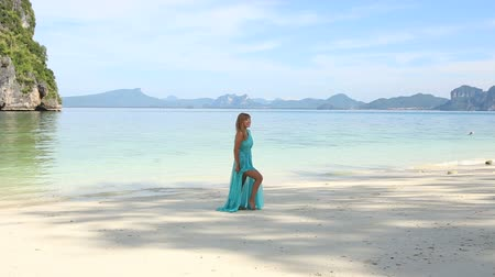 giydirmek : asian blonde girl poses on sand beach at background of tranquil transparent azure sea and island