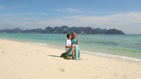 romantic couple : strong guy sits on stone with blonde asian girl on his knees they kiss and talk on beach near transparent azure tranquil sea against mountains Stock Footage