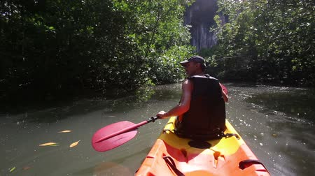 mangue : strong elder man rows kayak along river among mangrove trees turns aside and speak