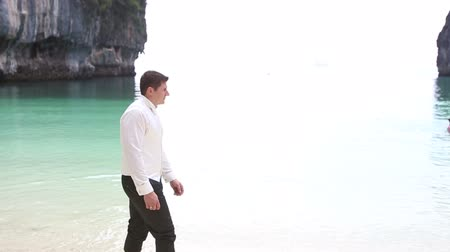 krawat : groom in black trousers and white shirt vest and tie walks on sand beach among cliffs against azure transparent sea