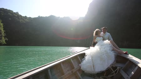 pelyhes : blonde bride in white wedding dress laughs with handsome groom sitting in longtail boat against mangrove trees at backlight