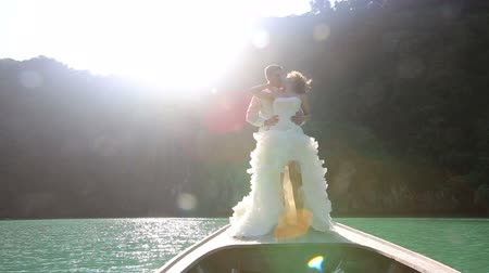 kıvırcık saçlar : blonde bride in wedding dress and handsome groom kiss standing on longtail boat at backlight