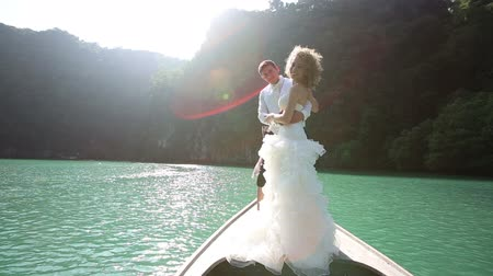 kıvırcık : curly blonde bride in long wedding dress turns from her back and laughs standing on longtail boat against mangrove trees