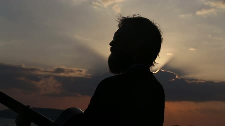 gitáros : silhouette of playing  guitarist at backlight against sun setting out off clouds