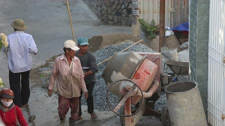 beton : NHA TRANG KHANH HOAVIETNAM  MAY 01 2015: Vietnamese builders pour sand road metal gravel and concrete into  concrete mixer to get cement solution on May 01 in Nha trang