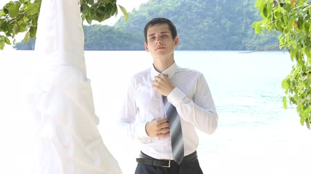 suit and tie : handsome groom in black trousers sets necktie straight on beach looking at brides wedding dress