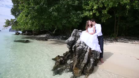 bochecha : handsome groom embraces brunette bride sitting on rock and kisses her cheek at background of beach and tree