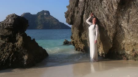 giydirmek : brunette bride in white wedding dress stands in transparent  shallow water and  leans on large cliff against islands