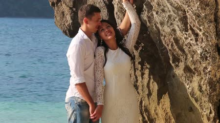 giydirmek : bride in wedding dress and groom stand and hug joining hands in shallow water by cliff