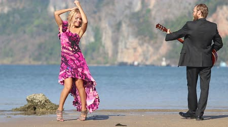 mar vermelho : bearded guitarist and  blonde girl look at each other following round circle against azure sea and cliffs