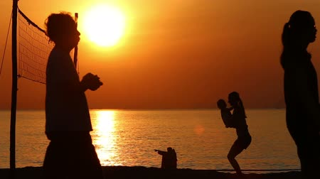 röplabda : silhouette of mother doing exercises with daughter at volleyball net on beach at sunrise above sea Stock mozgókép