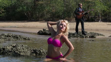 pink : blonde girl in pink swimsuit sits in sea basks in sun then feels cold against playing guitarist at low tide