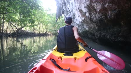 zadnice : old man in life-vest back-side view paddles on kayak down river in canyon among cliffs and mangrove jungle Dostupné videozáznamy