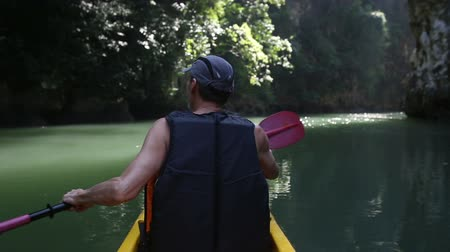 zadnice : european man backside view in safity vest rows on kayak out of jungle to freshwater in canyon