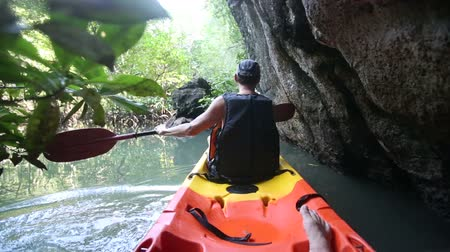 mangue : old man in life-vest back-side view paddles on kayak down river in canyon among cliffs and mangrove jungle Vídeos