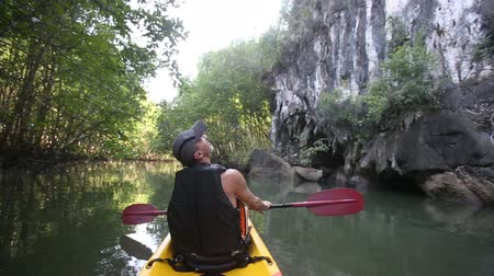 zadnice : old man in life-vest back-side view rows on kayak and looks upward at cliff near mangrove jungle