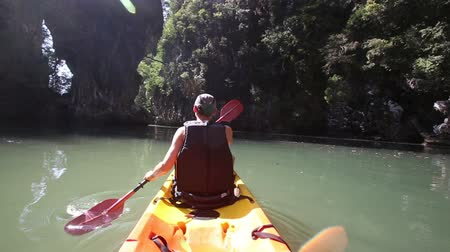 zadnice : european man backside view in life-vest rows on kayak to river mouth in canyon and splashes