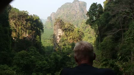 zadnice : european man backside view looks at canyon cliffs in Thailand jungle