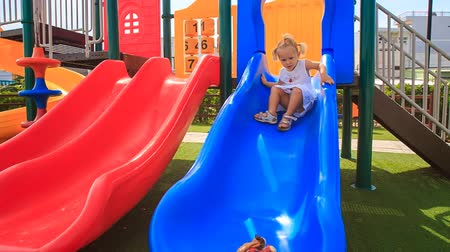 slayt : little blonde girl with hairtails in white dress slides down with toy from coloured slide on childs playground