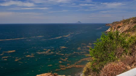 lovas : panorama of mountain road and pavement in Vietnam at background of azure sea and blue sky Stock mozgókép