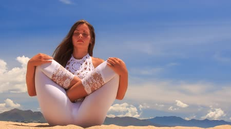гибкость : blonde girl in white lace costume meditates in yoga asana fetus on beach against azure sea and hills