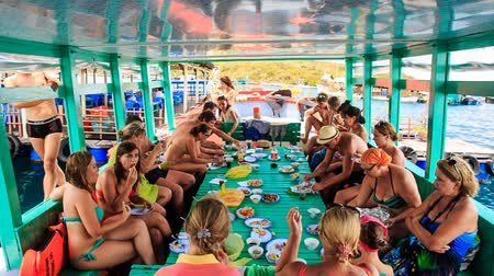 lunch : NHA TRANG, KHANH HOA  VIETNAM - SEPTEMBER November 2015: Group of tourists takes meal at large table on special tourist vessel in open sea in Vietnam on September 11 in Nha trang