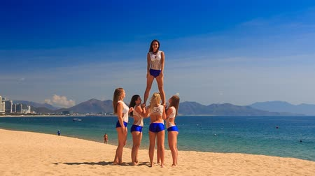 piramit : squad of six cute cheerleaders in white blue uniform performs half stunt pyramid on beach against azure sea