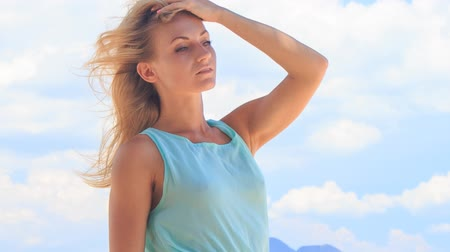 uzun : portrait of european slim blonde girl in light azure frock smoothing hair under wind against white clouds Stok Video