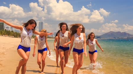 духи : cute cheerleaders in white blue uniform jump gambol wave hands in shallow water on beach against azure sea Стоковые видеозаписи