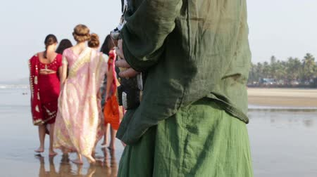 caucasiano : guy in green clothes holds ritual mask behind back to frighten European girls in Indian national dresses on beach Vídeos