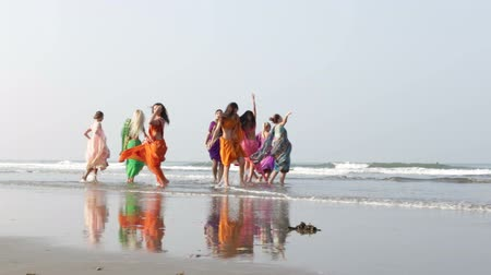 kaukázusi : girls in colourful Indian national dresses run out to wet sand beach and dance in shallow azure water Stock mozgókép