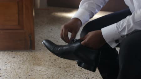 cipőfűző : man in white wedding shirt and black trousers puts on black shoes and ties shoe-laces in bow sitting on bed Stock mozgókép