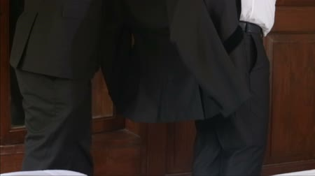 smokin : man in black suit helps groom in white shirt to put on tuxedo in front of mirror