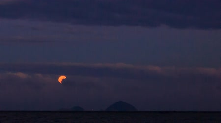 mehtap : yellow moon from behind clouds in dark blue sky above sea bay Stok Video