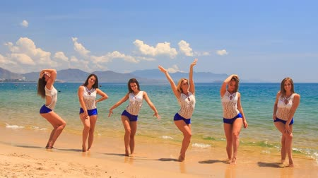 step : cute cheerleaders in white blue uniform step out of shallow water and stand in line on wet beach against azure sea